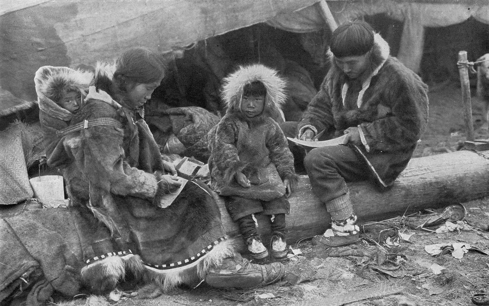 Black and white photograph of traditional inuit sitting on a log
